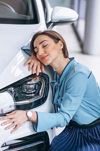 Junge Frau umarmt Auto